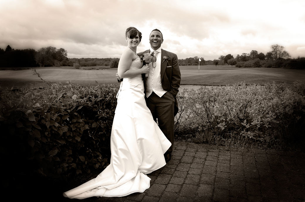 A happy newly-wed couple wedding photo taken on the patio during a moment of respite on a stormy wet day captured by Surrey Lane wedding photographers at Surrey Downs Golf Club