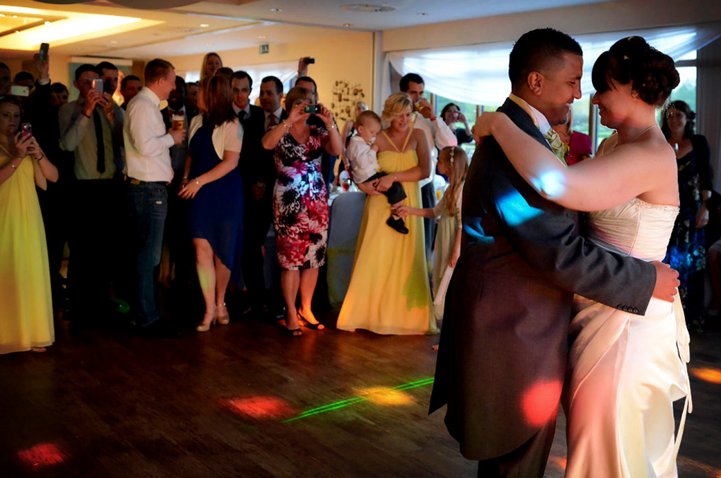 Bride and Groom in this intimate first dance wedding picture moment taken on the dance floor of the Willow Suite at Surrey Downs Golf Club a fine Surrey wedding venue