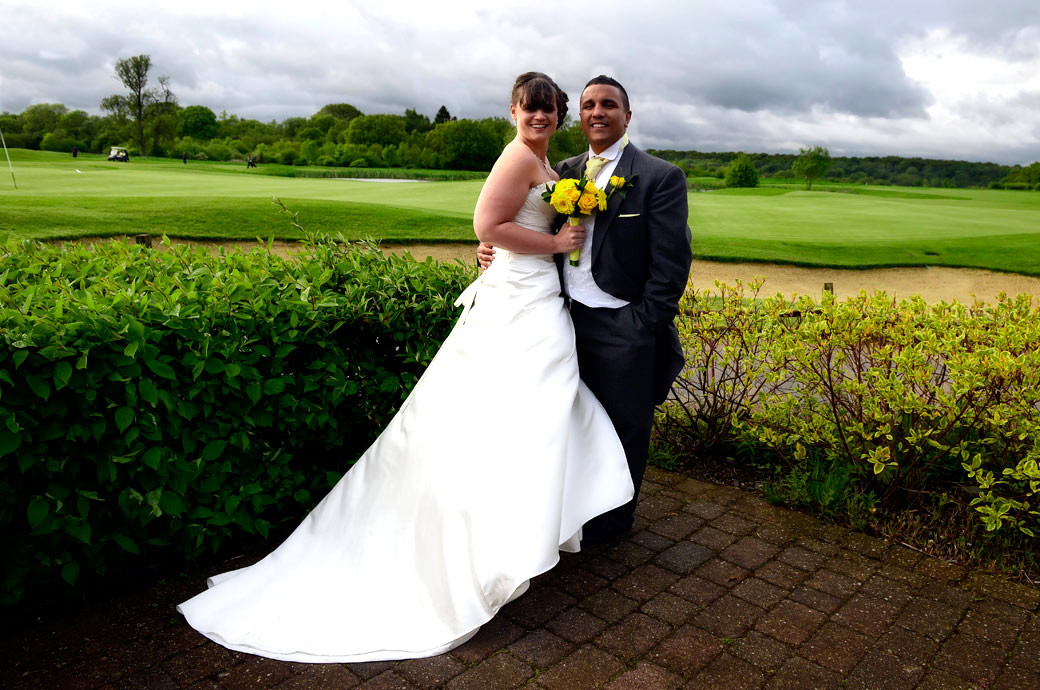 Smiling newly-weds just before the rain starts again wedding photograph taken on the patio outside the Surrey Downs Golf Club a lovely Surrey wedding venue in Kingswood
