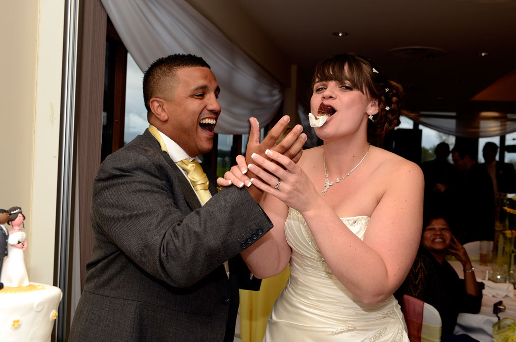 Fun wedding photograph of a laughing bride with a mouth full of wedding cake captured by Surrey Lane wedding photography at Surrey Downs Golf Club