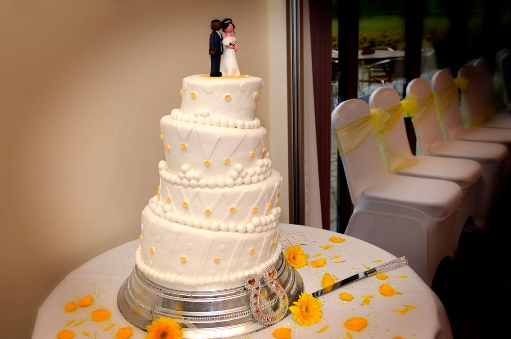 A delicate yellow dressed wedding cake wedding photo taken in the Willow Suite at Surrey wedding venue Surrey Downs Golf Club