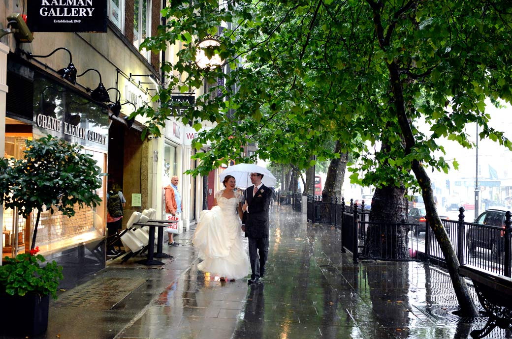 Romantic walk along pavement for the newlyweds under a white umbrella in the pouring rain wedding photographer Surrey
