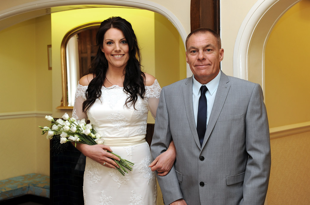 Beaming Bride and her Father stand arm in arm and pose in this delightful wedding picture for their Surrey Lane wedding photographer in the hall at Sutton Register Office