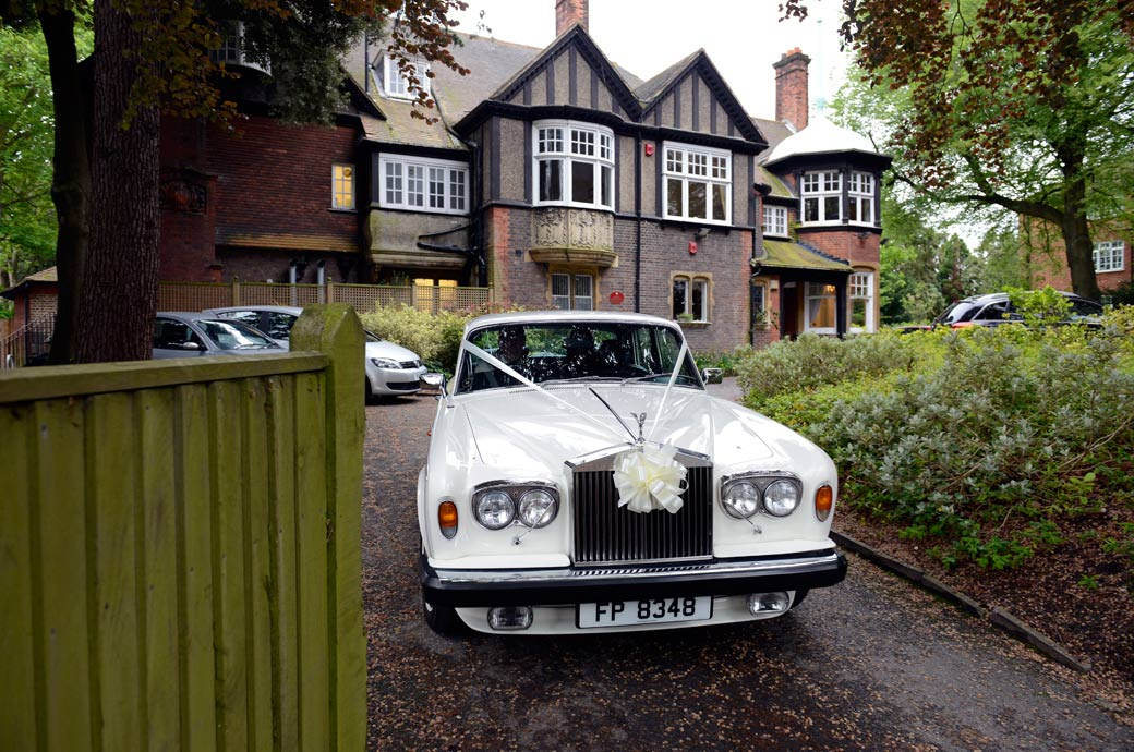 A  wedding photograph of a classic white Rolls Royce carrying the newly-weds from Sutton Register Office to the reception captured by Surrey Lane wedding photography