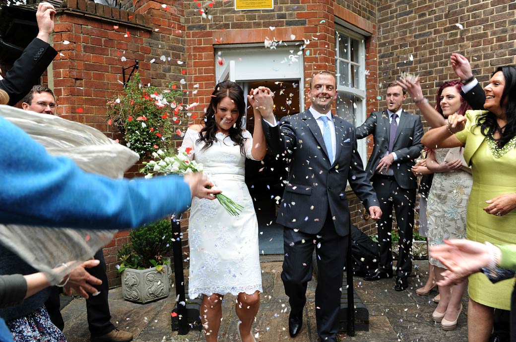 Holding hands as they walk through the shower of confetti in this fun wedding picture taken outside Sutton Register Office by Surrey Lane wedding photography