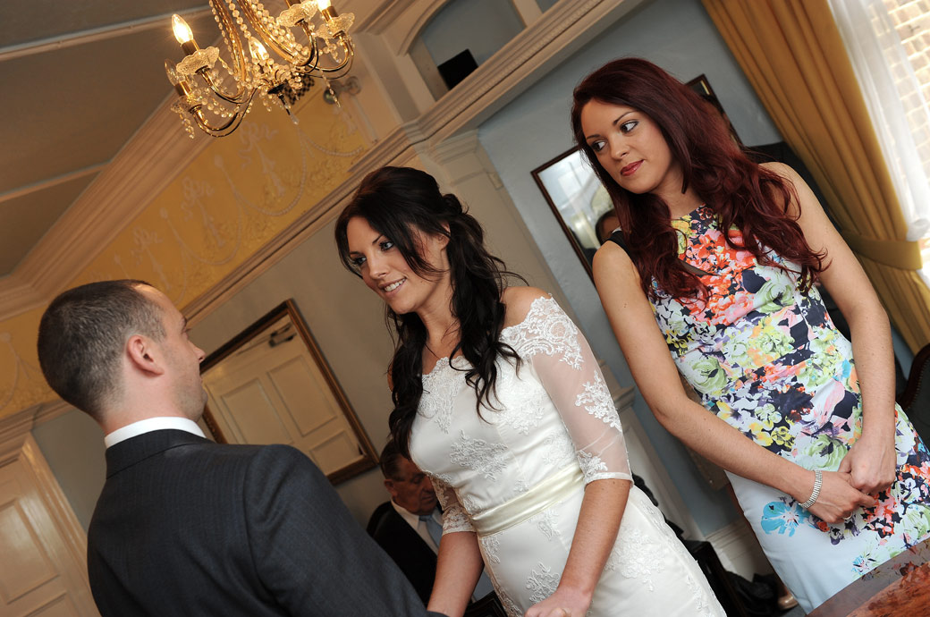 Eyes of the Bride and sister focus on the Groom in this  touching wedding picture captured at Surrey wedding venue Sutton Register Office in the Drawing Room