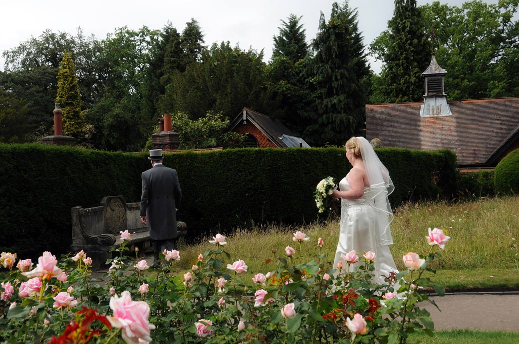 Bride follows the Groom to the stone bench is this lovely romantic wedding picture taken in Coombe Wood Gardens at The Chateau in Surrey