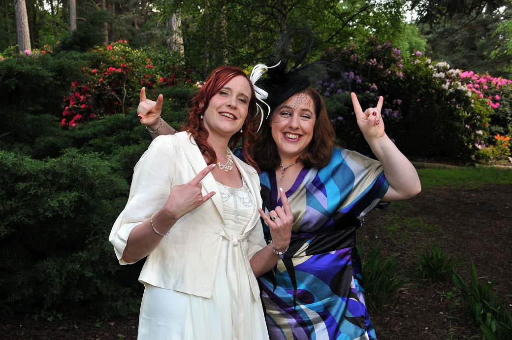 Bride and friend posing for the photographer in this fun Rock Chicks wedding photo taken in Coombe Wood Gardens at Surrey venue The Chateau
