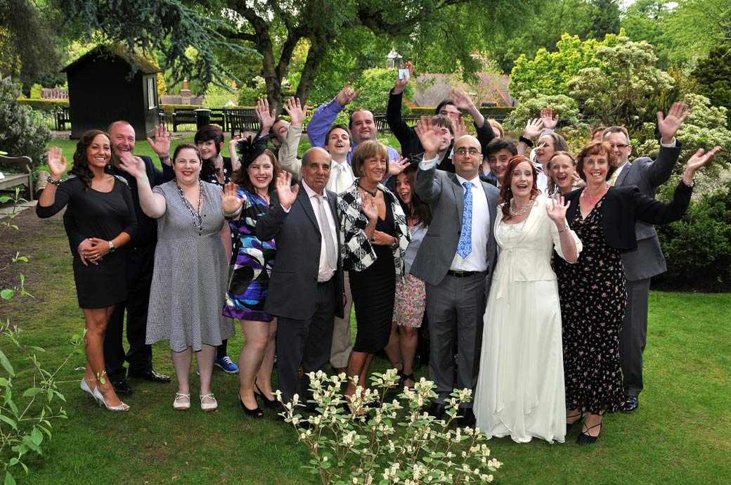 Everyone at the Surrey wedding venue The Chateau waving in this group wedding photo taken in the beautiful Coombe Wood Gardens