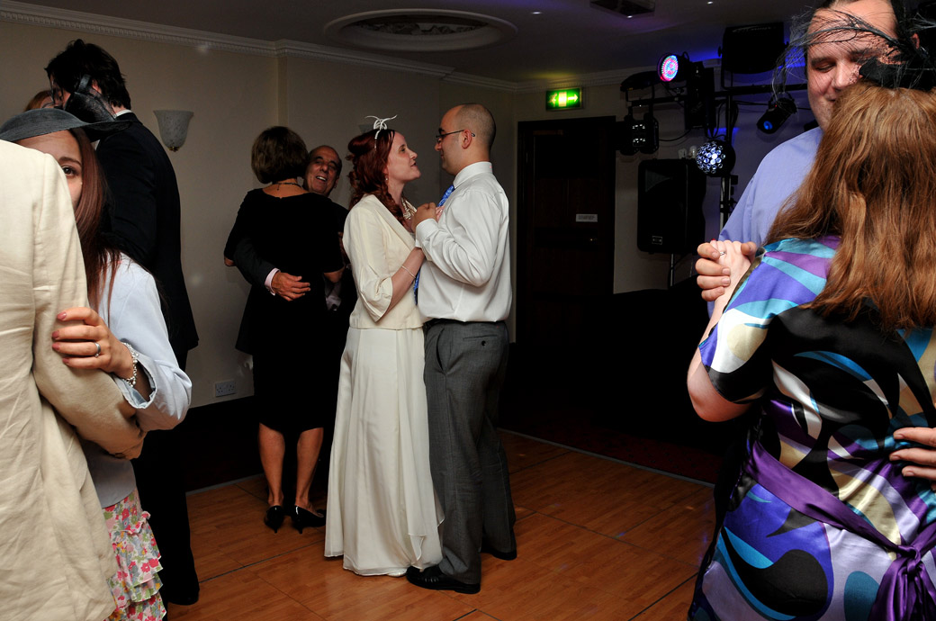 Newly-wed couple are joined on the dance floor in this informal wedding picture taken  in the Park View Suite at Surrey wedding venue The Chateau