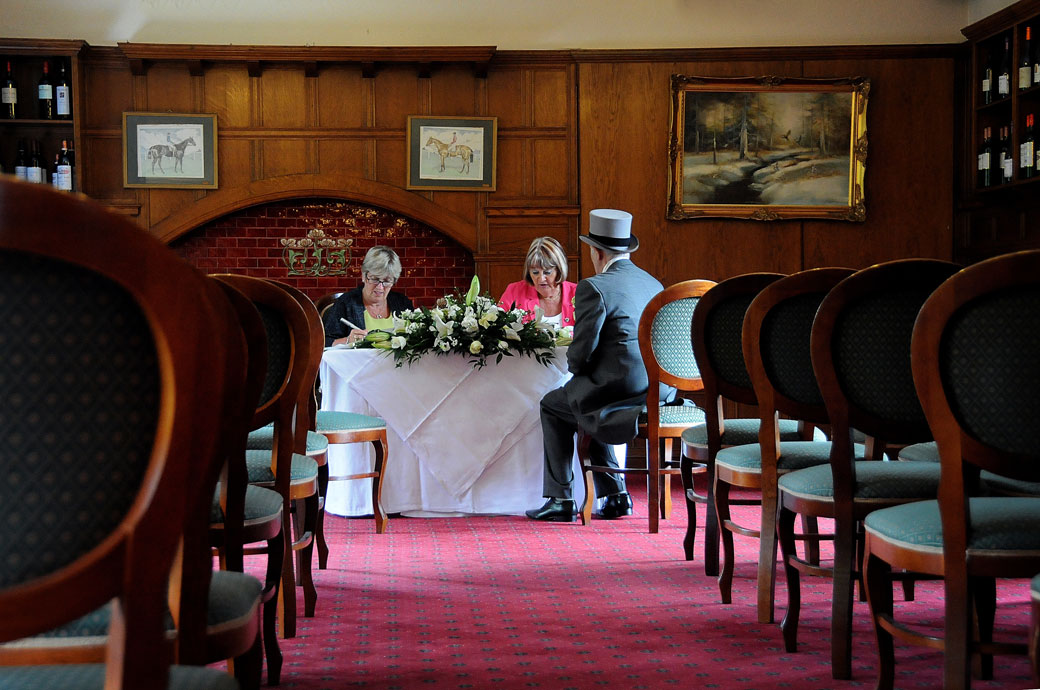 The Groom being interviewed by the Registrars in this discrete wedding photograph taken in panelled restaurant of Surrey wedding venue The Chateau