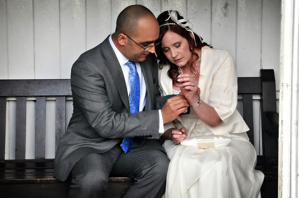 Groom helps his Bride adjust her bracelet in this sweet wedding picture by Surrey Lane wedding photographer at The Chateau in Coombe Wood Gardens