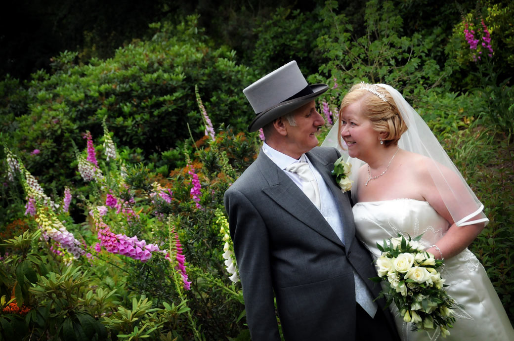 An intimate moment with the Bride and Groom in this wedding photo taken in amongst the Foxgloves at The Chateau in Coombe Wood Gardens Surrey