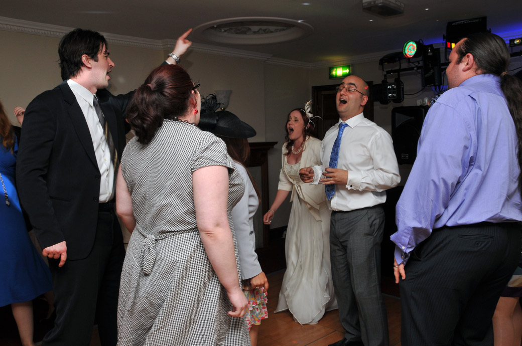 Bride and Groom in full flow as they sing in this wedding photo taken on the Park View Suite dance floor of The Chateau in Surrey