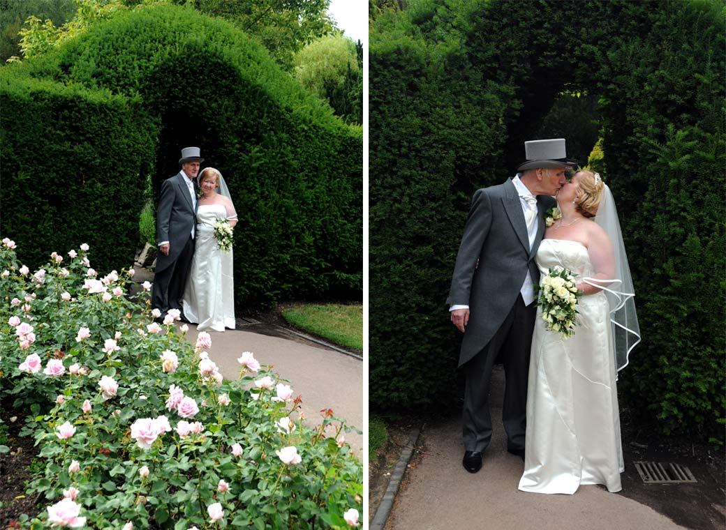 Standing by the hedge arch and having a kiss captured in these two wedding photographs taken at The Chateau by Surrey Lane wedding photographers