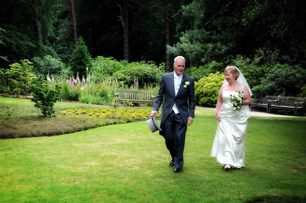 Newly-married couple take a stroll across the lawn in Coombe Wood Gardens at The Chateau captured in this wedding picture taken in Croydon Surrey