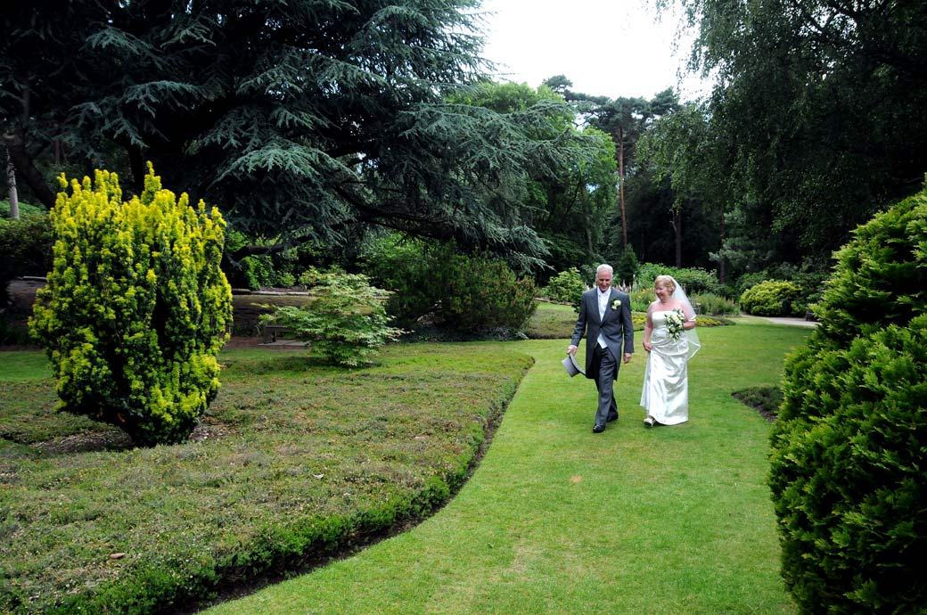 Nonchalantly walking across the lawn in this wedding photo taken as the newly-weds walk through Coombe Wood Gardens to The Chateau in Surrey
