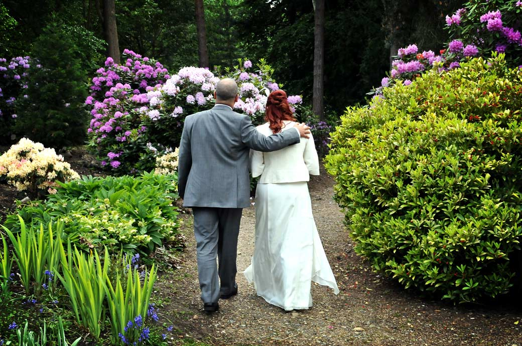 Happy couple walk together in the beautiful and colourful Coombe Wood Gardens in this wedding picture taken at Surrey wedding venue The Chateau