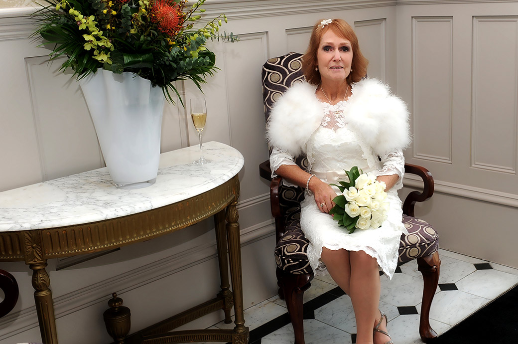 An elegant lovely Bride smiles as she waits for the groom to come down the grand stairs at The Petersham Hotel Richmond a popular and intimate Surrey wedding venue
