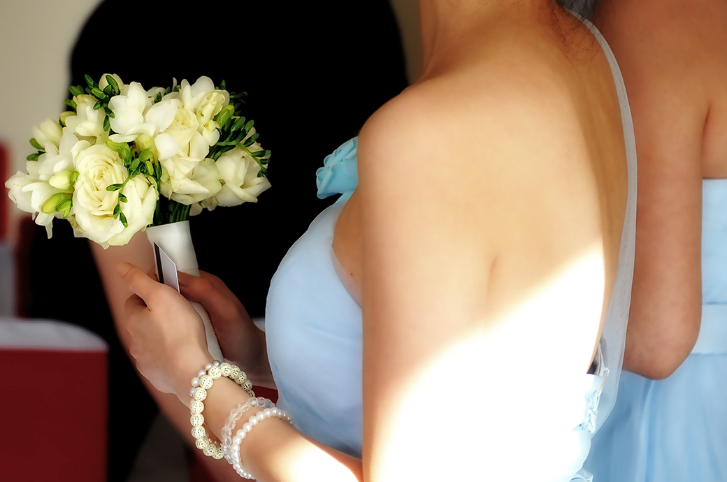 Close up wedding photograph of a bridesmaid in blue holding her wedding bouquet ready for the arrival of the Bride at the fabulous Petersham in Richmond Surrey