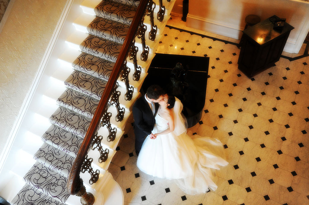 Wedding photo taken from top of the stairs looking down on the newlyweds as they romantically kiss by the piano at The Petersham Hotel a grand Surrey wedding venue in Richmond