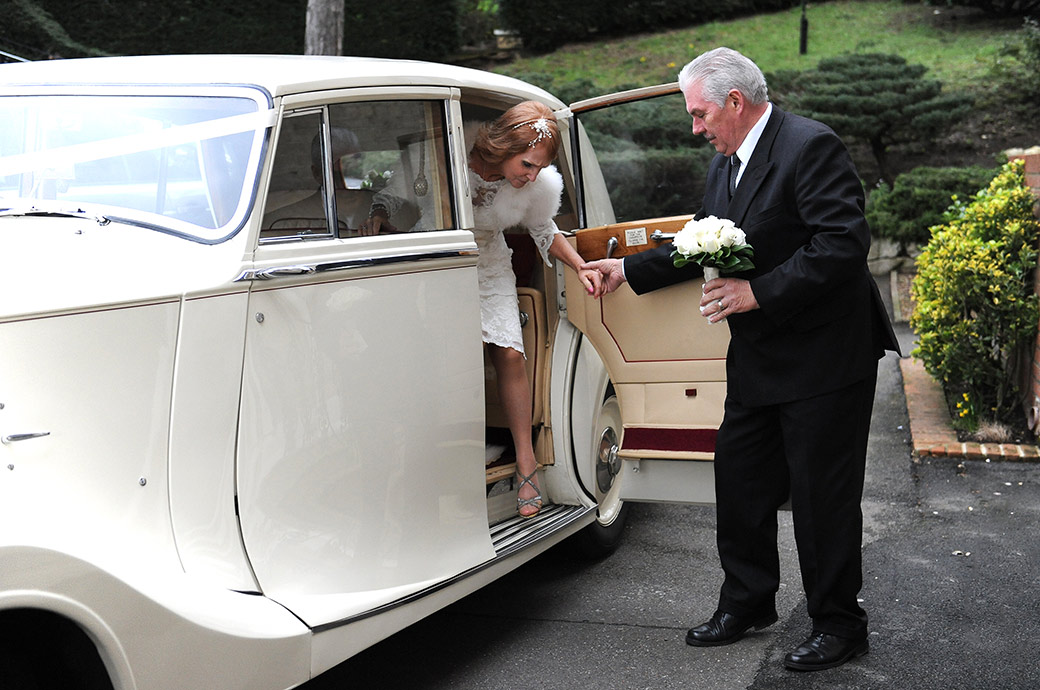 Wedding photograph of the bride being helped out of a large classic white Rolls Royce wedding car at The Petersham Hotel Richmond Surrey by the gentleman Chauffeur