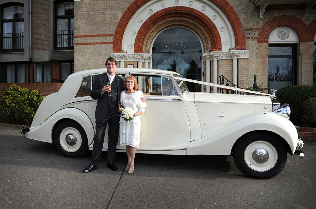Proud groom standing with his radiant Bride in front of their classic white Rolls Royce outside Surrey wedding venue The Petersham Hotel in Richmond with champagne to celebrate