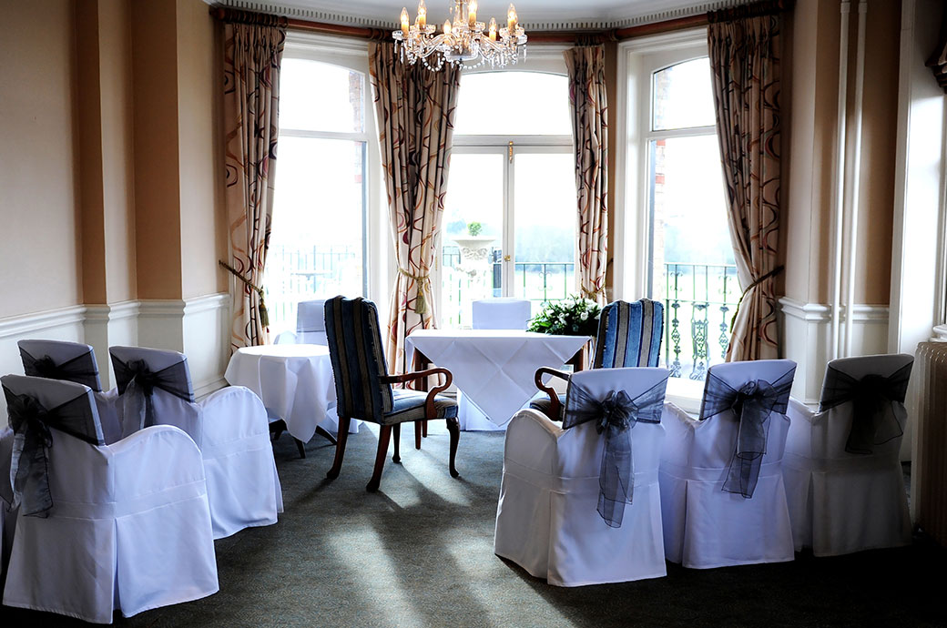 An intimate wedding ceremony set up in the River Room with its fabulous views over the meandering Thames at The Petersham Hotel a fine Surrey wedding venue in Richmond