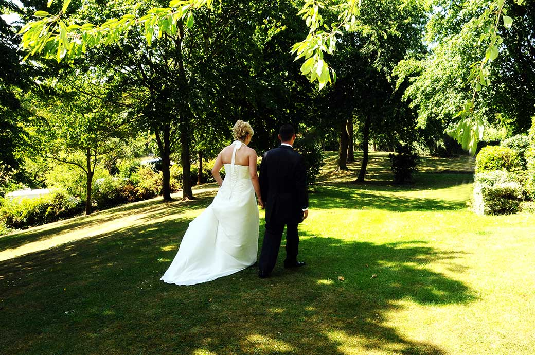 Bride and groom at Surrey wedding venue The Petersham Hotel in Richmond walking hand in hand a cross the lawn on a bright summer wedding day