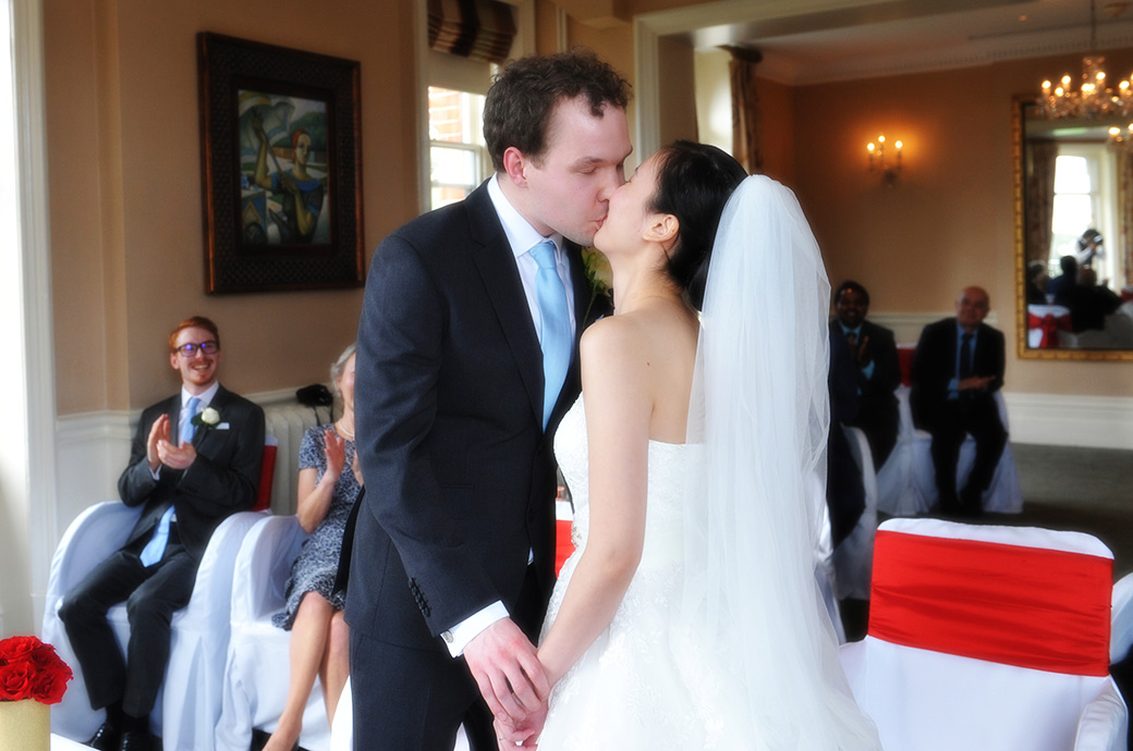 Wedding photograph of the Bride and groom at The Petersham Hotel in Richmond Surrey holding hands and kissing as they become husband and wife