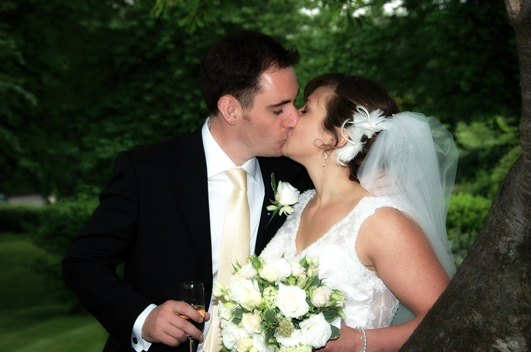Beautiful romantic kiss captured at Surrey wedding venue The Petersham Hotel in Richmond by a Surrey Lane wedding photographer on the lawn amongst the trees