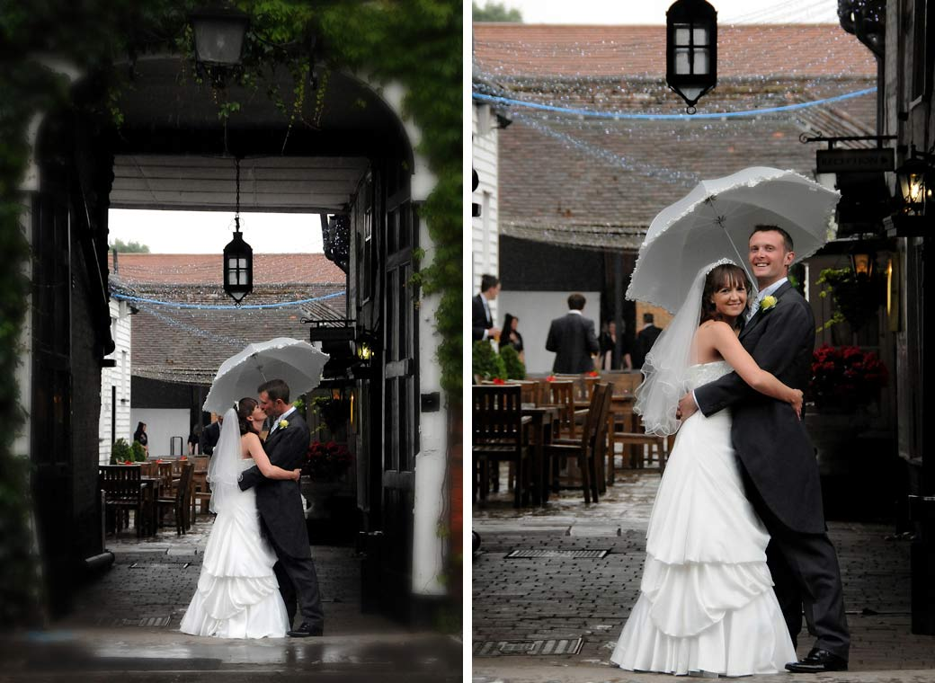 Lovely smiling and kissing wedding photos taken in the ivy covered entrance of The Talbot an historic Surrey wedding venue in picturesque Ripley