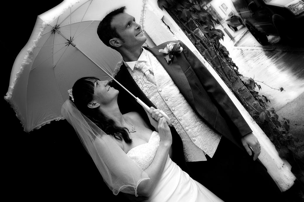 Beautiful atmospheric wedding photo of newly-weds watching the world go by under an umbrella by Surrey lane wedding photography at The Talbot, Ripley