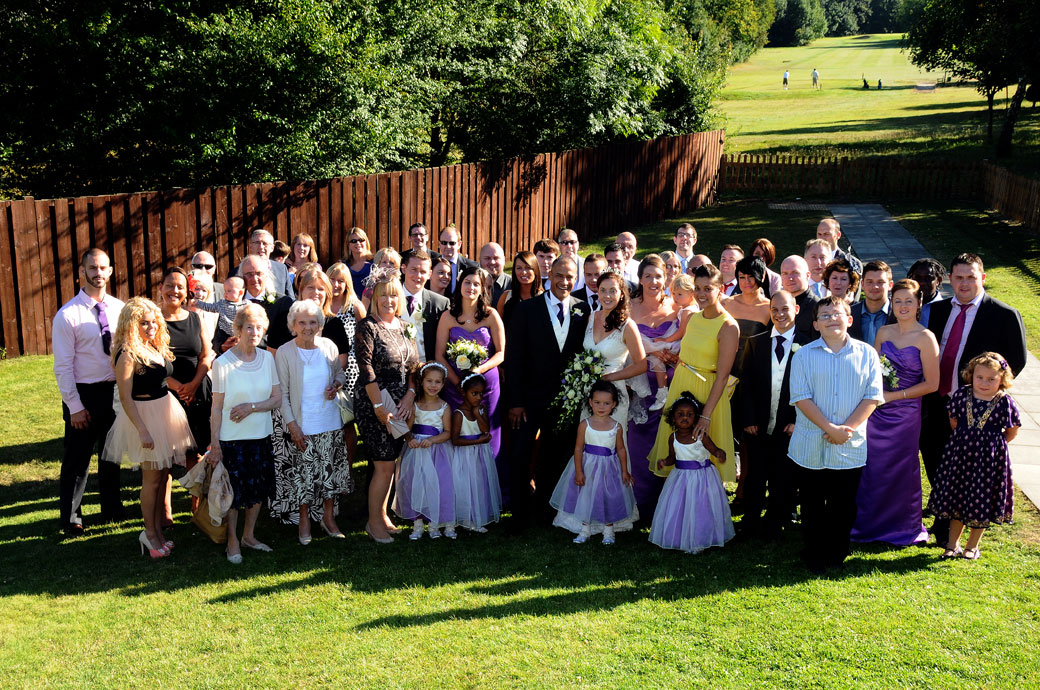 Everyone at the wedding group wedding photograph taken at Surrey wedding venue The Oaks Golf Centre in Carshalton