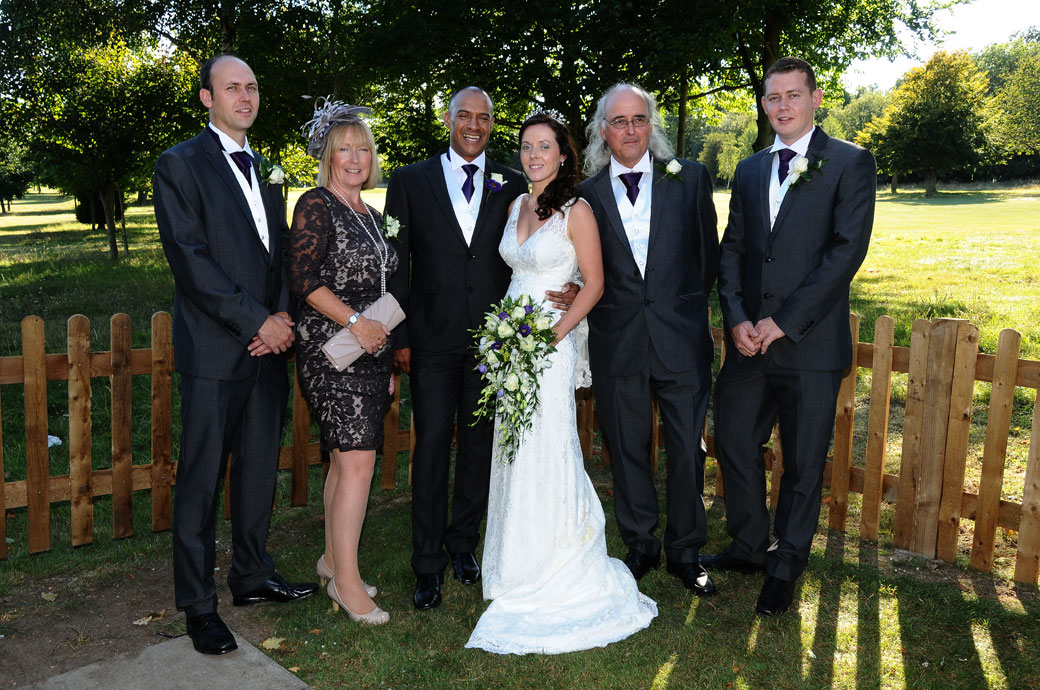 Relaxed family group wedding photograph taken on the lawn at The Oaks Carshalton by Surrey Lane wedding photographers