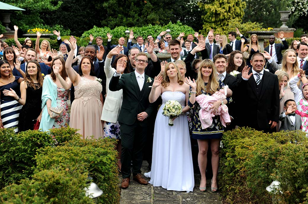 Happy Bride and groom along with guests captured by a Surrey Lane wedding photographer Warren House in Kingston waving as they stand by the Victorian water fountain