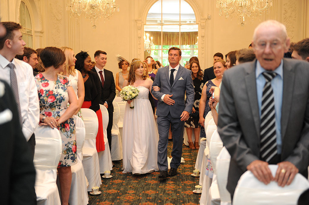 Guests' heads turn as a nervous and excited Bride at Surrey wedding venue Warren House in Kingston walks down the aisle of the marriage ceremony room on the arm of her uncle