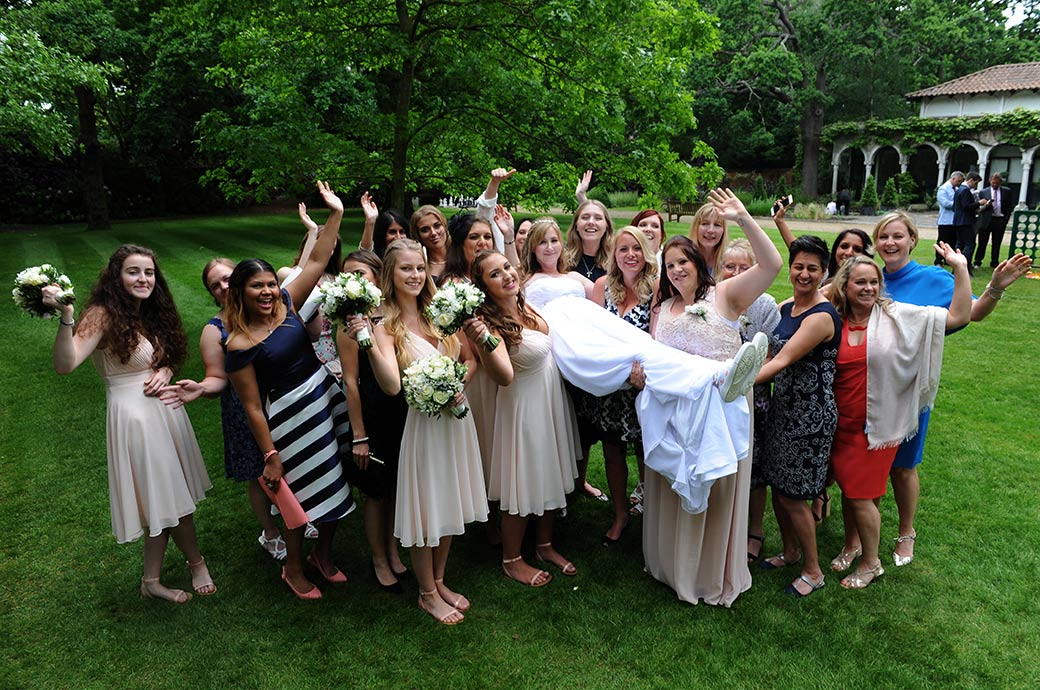 Ladies lift the bride up into the air and wave for the Surrey Lane wedding photographer captured at Warren House in Kingston during the fun reception drinks