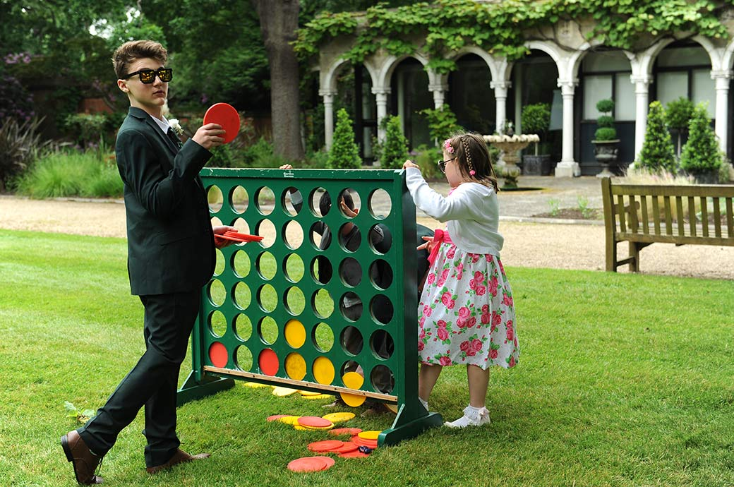 A wedding photograph of children at Surrey wedding venue Warren House playing a giant garden Connect Six game out on the lawn during the drinks reception