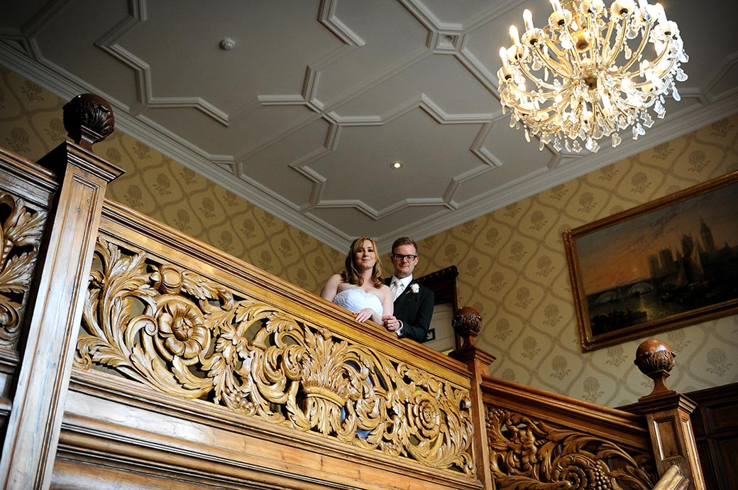 Wedding photo of a happy and content Bride and groom at Warren House in Kingston Surrey as they look down from the beautifully ornate wooden staircase