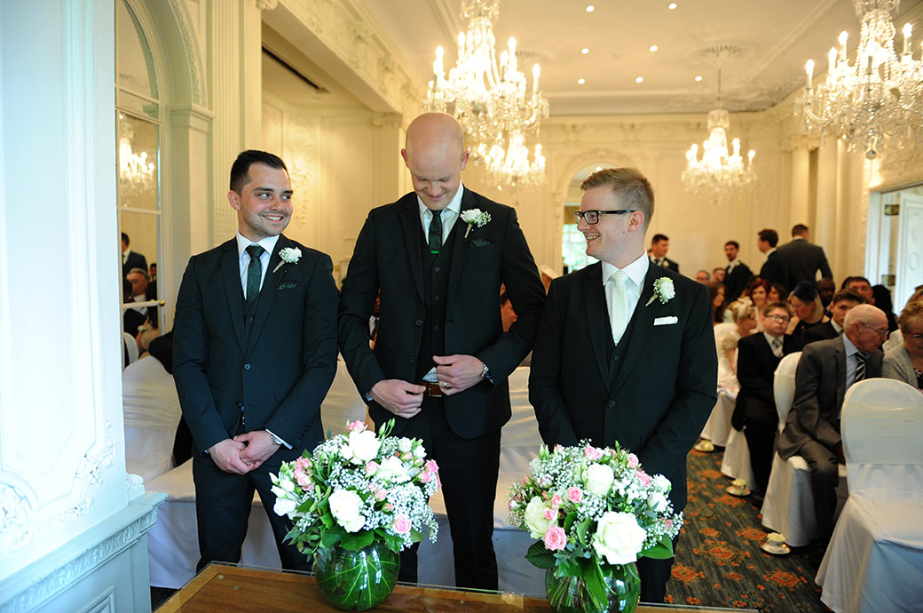 A smiling Groom and usher watch the best man adjust his jacket at Surrey wedding venue Warren House Kingston as they await the registrar in the marriage ceremony room