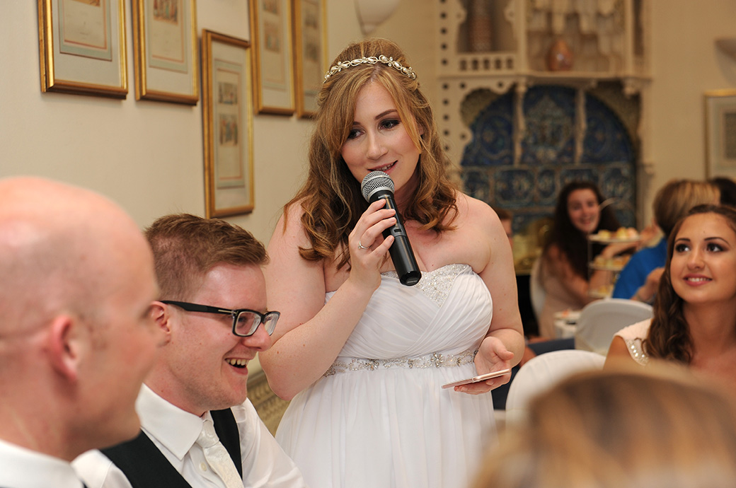 Close up wedding photograph from Warren House in Kingston Surrey of a smiling Bride with microphone in hand talking about her smiling husband during her wedding speech