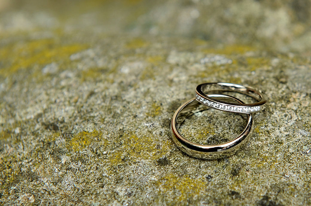A close up wedding photo of shiny glistening wedding rings placed on some old weather beaten stones captured by a Surrey Lane wedding photographer in the Warren House gardens