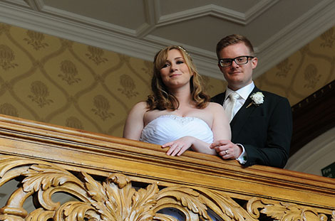Serene young Bride and groom looking down from the beautifully ornate wooden staircase at the wonderful Warren House Surrey wedding venue in Kingston Upon Thames