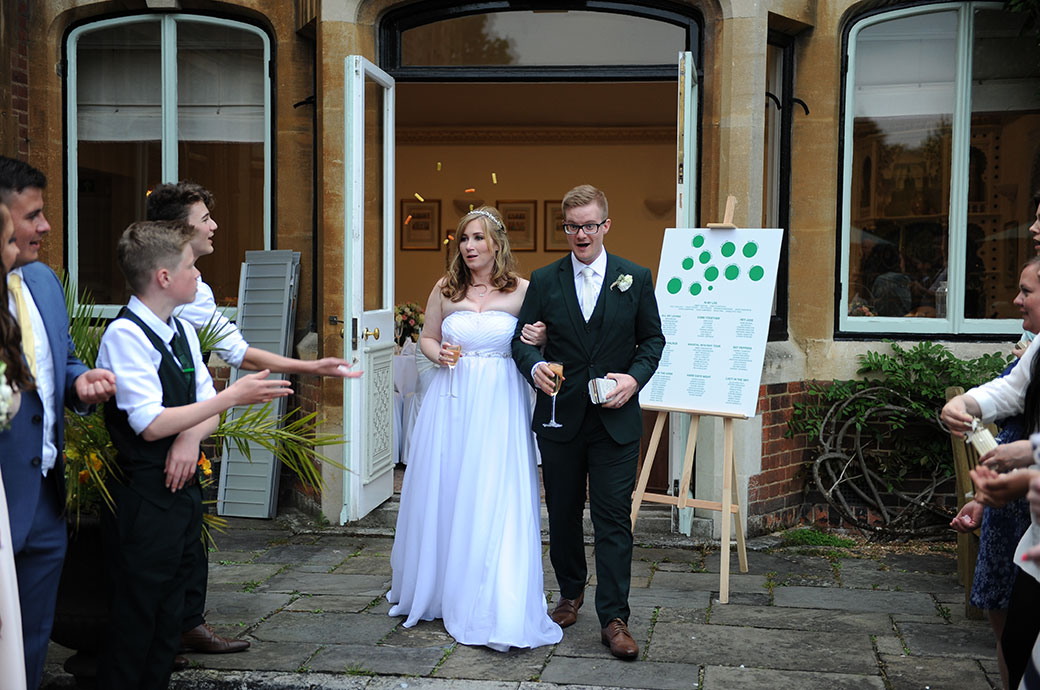 Bride and Groom start their walk arm in arm and with champagne in hand towards the guests with their confetti captured in Surrey at Warren House out on the terrace