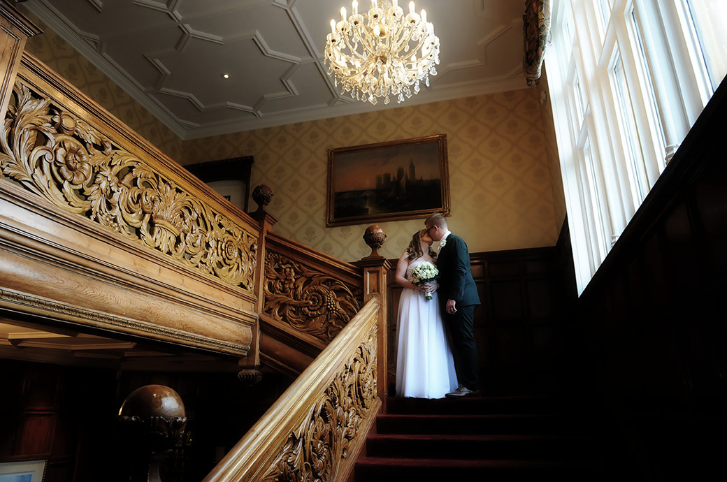 A romantic moment captured at Surrey wedding venue Warren House in Kingston Upon Thames as a bride and Groom kiss at the top of the magnificent wooden staircase