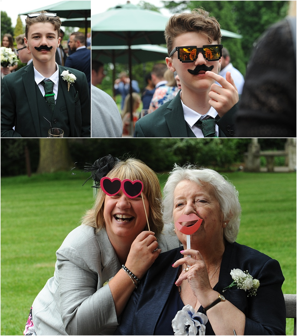 Wedding guests having fun as they disguise themselves with moustaches, sun glasses and lips at the relaxed and  tranquil Warren House wedding venue in Kingston Surrey