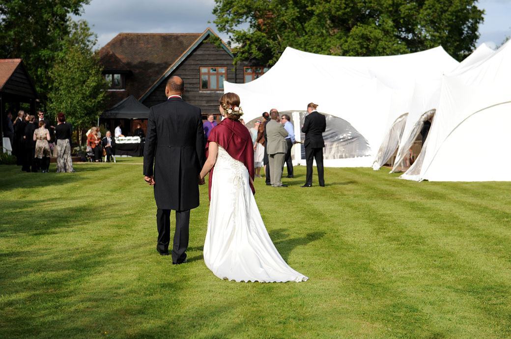 Bride and groom walk down the Main Lawn hand in hand to the awaiting reception guests after some romantic wedding photos at Westmead Events in Redhill Surrey