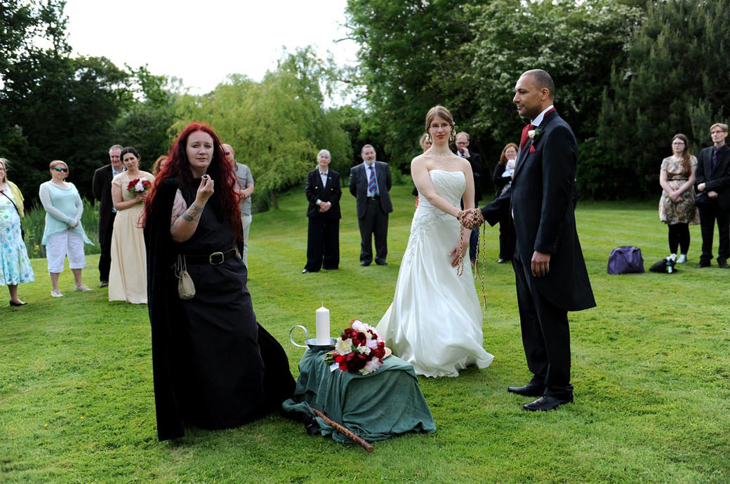 Bride and groom standing with their hands fastened as the Druid Priest Cat Treadwell turns to the exchanging of rings  at Westmead Events  Surrey on the Main Lawn area