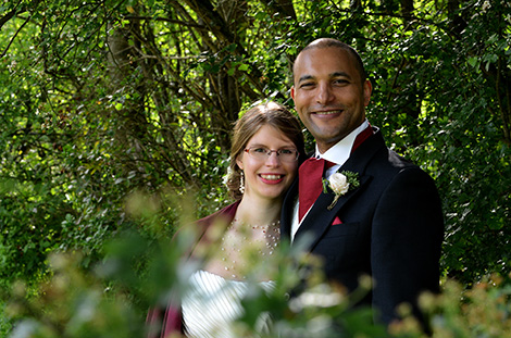 Smiling Bride and Groom captured in this wedding photo taken through the trees and bushes at Surrey wedding venue Westmead Events in Redhill